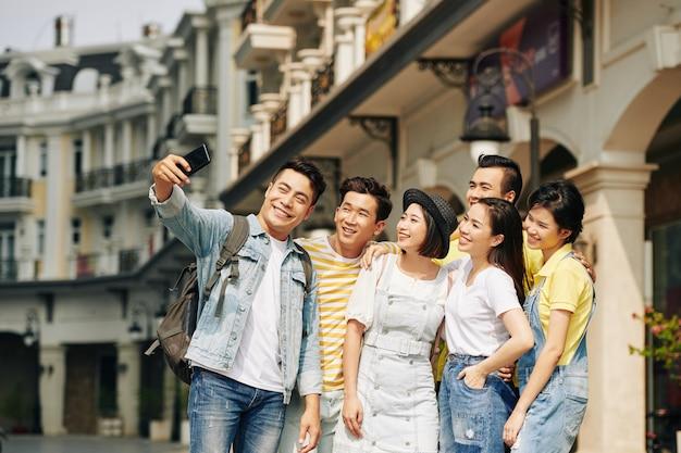 Homme prenant selfie avec des amis dans le centre-ville