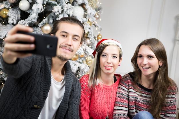 Homme prenant selfie d'amis en face de l'arbre de noël