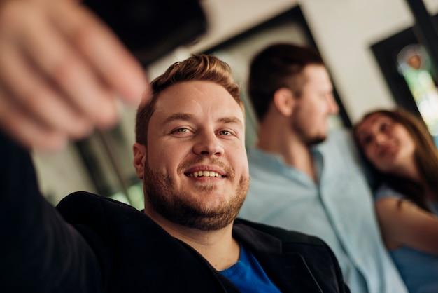 Homme prenant selfie avec des amis à l'intérieur