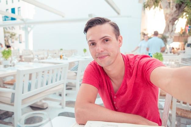 Homme prenant selfie assis dans un café en plein air.