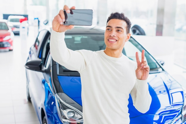 Homme prenant selfie chez un concessionnaire automobile