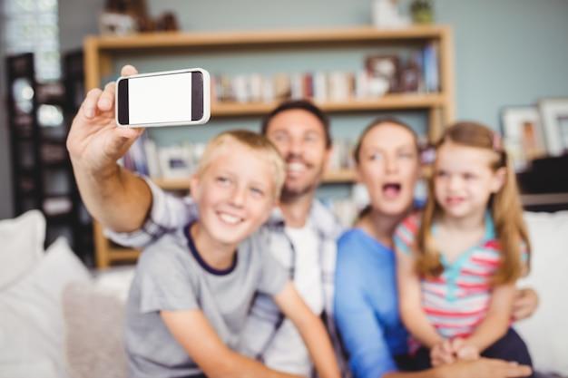 Homme prenant selfie de famille avec téléphone portable