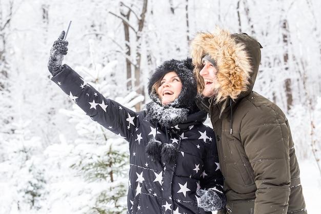 Homme prenant selfie photo jeune couple romantique sourire neige forêt hiver en plein air.