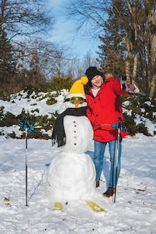 Homme prenant le selfie avec la saison d'hiver de bonhomme de neige de skieur