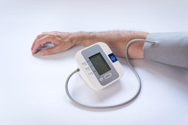 Homme prenant la tension artérielle en photo avec fond blanc.