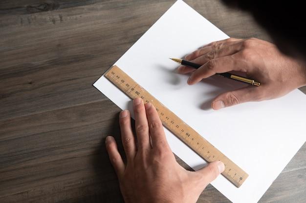 Un homme prend des mesures sur papier avec une règle et un crayon