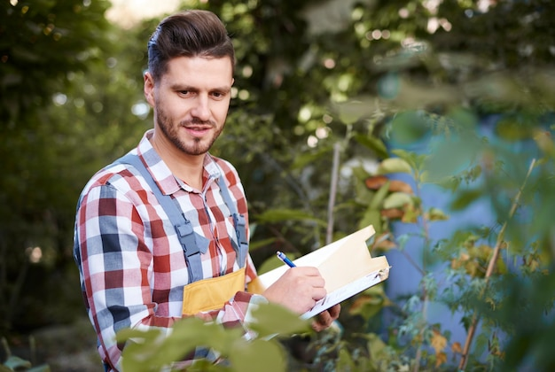 L'homme prend des notes sur le presse-papiers tout en vérifiant les fleurs