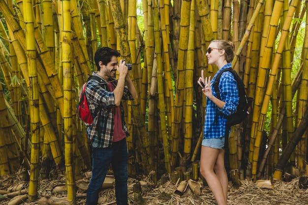L'homme prend une photo de petite amie dans une forêt de bambous