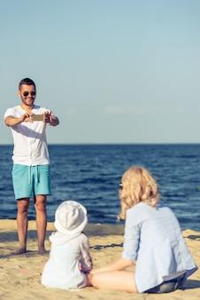 L'homme prend en photo sa belle femme et sa petite fille.