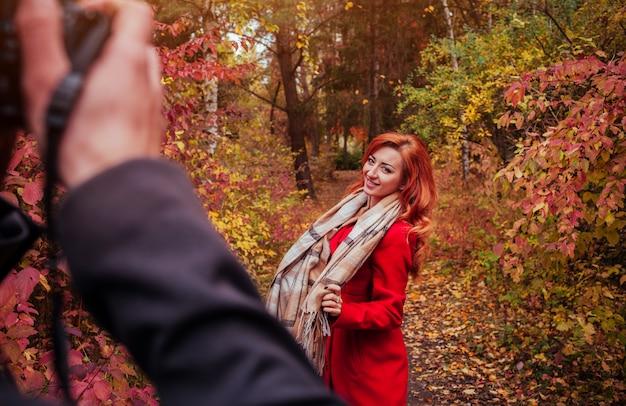 Homme prend une photo de sa petite amie à l'aide de la caméra dans la forêt d'automne