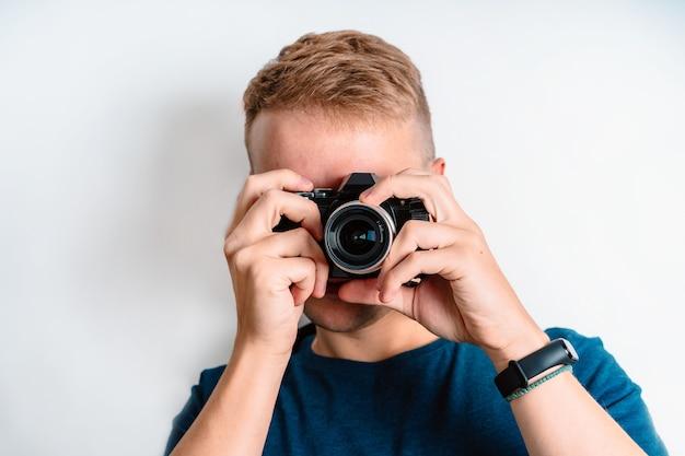 L'homme prend des photos et regarde à travers le viseur, isolé