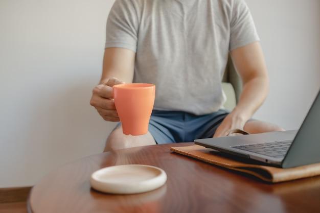 L'homme prend une tasse de café tout en travaillant sur son ordinateur portable.