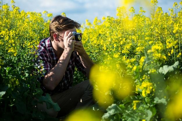 Homme, prendre photo, depuis, appareil photo, dans, champ moutarde