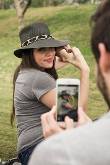 Homme, prendre, photo, de, elle, petite amie, faire coeur, à, main, depuis, téléphone portable
