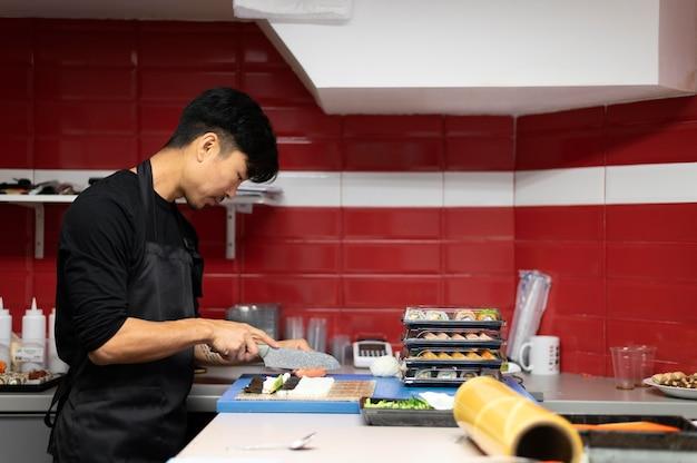 Homme préparant une commande de sushi à emporter
