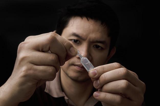 Homme préparant la médecine des gouttes pour les yeux guérir sa douleur aux yeux avec fond noir