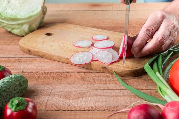 Homme préparant une salade de radis frais à la maison