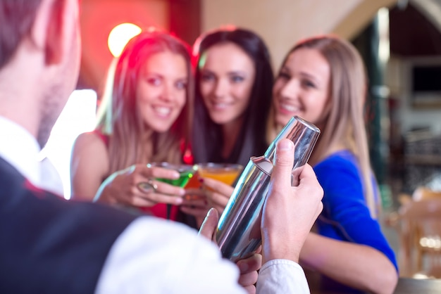 Un homme prépare de délicieux cocktails pour toutes les filles.