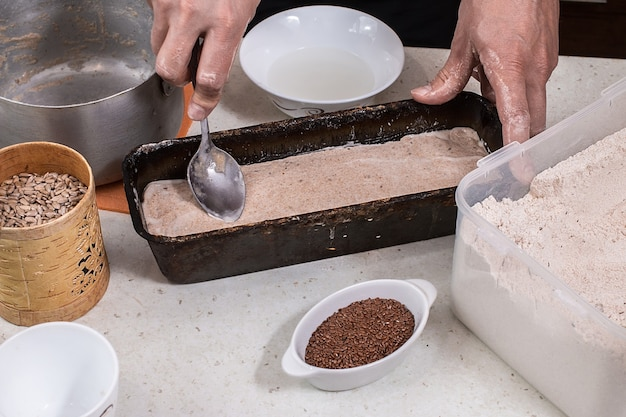 L'homme prépare la pâte à pain sur table en bois