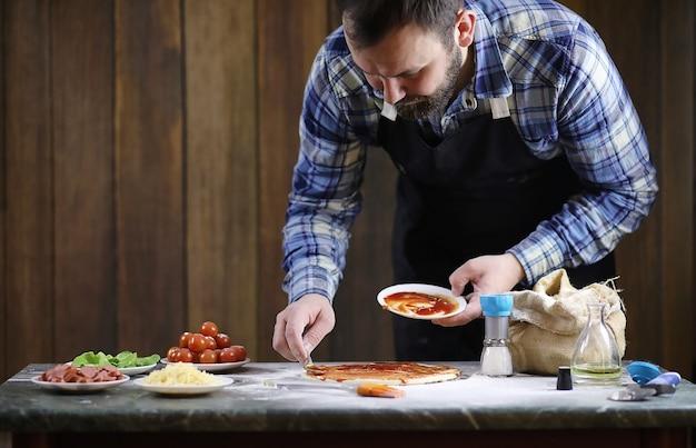 Un homme prépare une pizza, pétrit la pâte et met les ingrédients