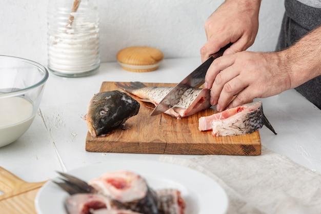 Homme prépare des poissons de rivière carpe dans la cuisine à domicile. cuisiner des aliments sains et diététiques