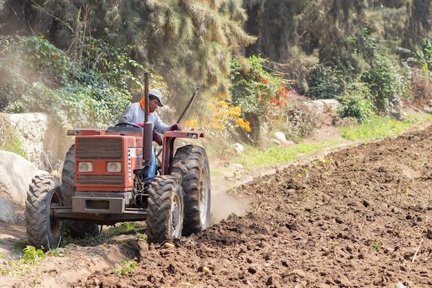 L'homme prépare la terre pour la récolte avec le tracteur à la ferme