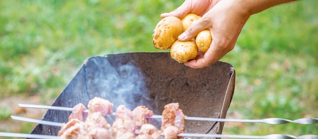 L'homme prépare la viande de barbecue avec des pommes de terre