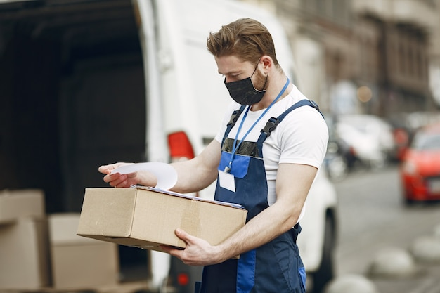 Homme près du camion. guy en uniforme de livraison. homme dans un masque médical. concept de coronavirus.