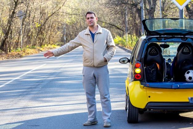 L'homme près de sa voiture attend de l'aide