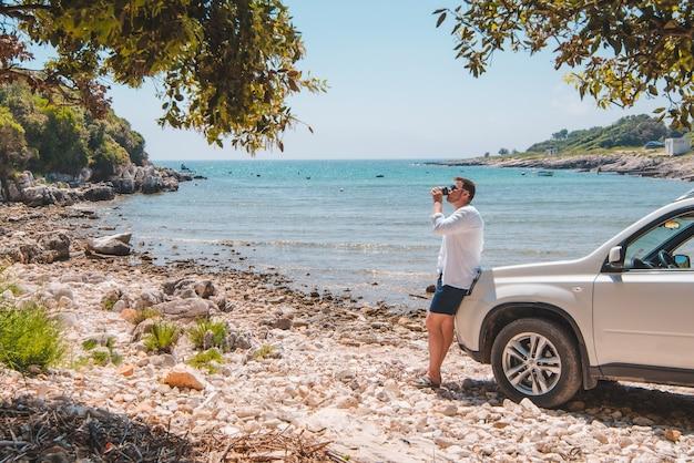 Homme près de la voiture suv blanche au concept de voyage de liberté de plage de mer d'été