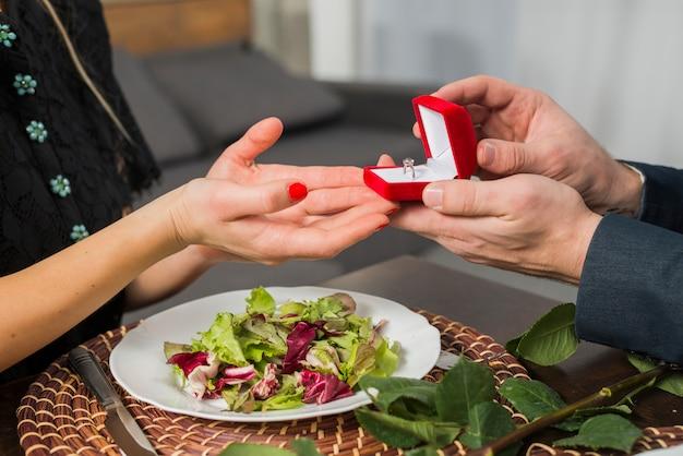 Homme présentant une boîte-cadeau avec anneau pour femme à la table avec une plaque