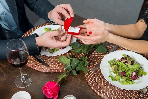 Homme présentant une boîte-cadeau pour femme à table avec assiettes, rose et verre