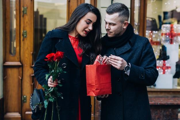 Homme présentant un cadeau à jolie dame