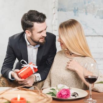 Homme présentant un cadeau à sa petite amie