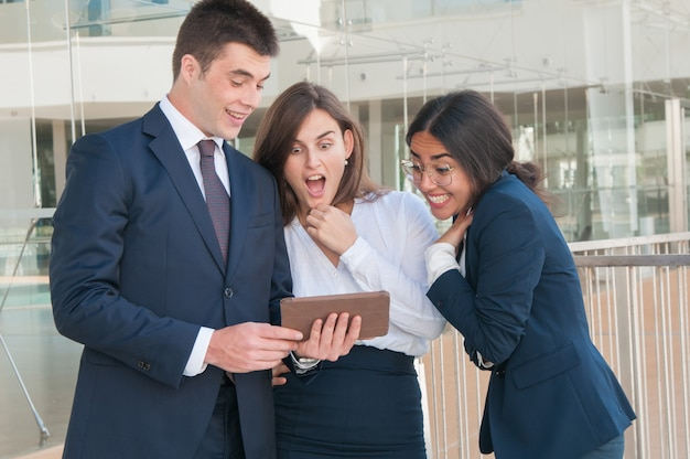 Homme présentant des données de collègues sur tablette, ils ont l'air choqué