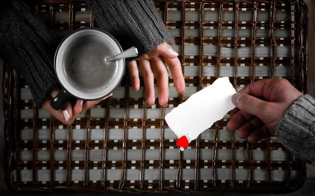 L'homme présente une fille qui boit un cadeau de café le jour de la saint-valentin
