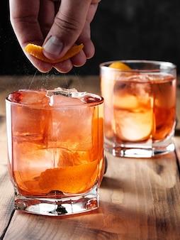 Un homme presse le zeste d'une orange sur des verres avec un cocktail negroni. photo verticale.