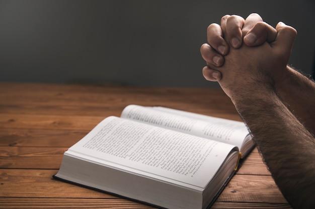 Un homme priant sur un livre sur une surface sombre