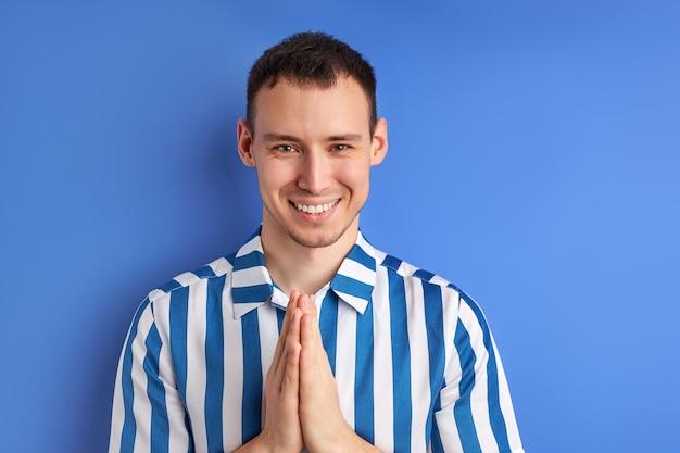 Homme priant main dans la main, regarde la caméra en souriant, ayant un sourire charmant.