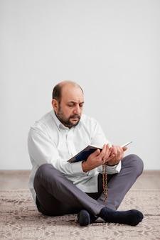 Homme priant sur le sol à l'intérieur