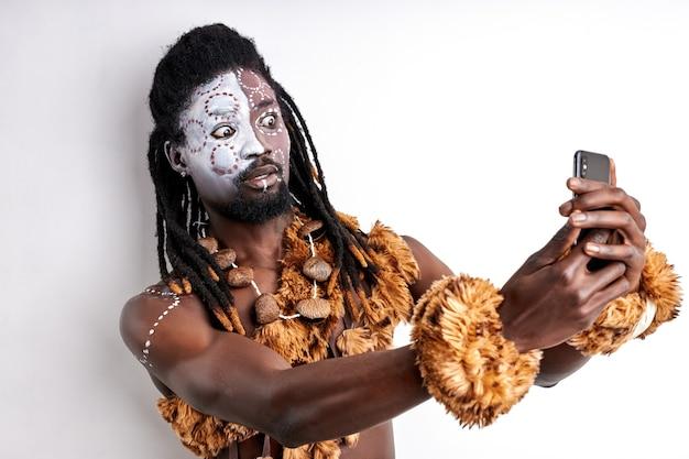 Homme primitif africain utilisant un téléphone portable, il est surpris par les technologies modernes, réagit émotionnellement, porte des vêtements et du maquillage ethniques nationaux