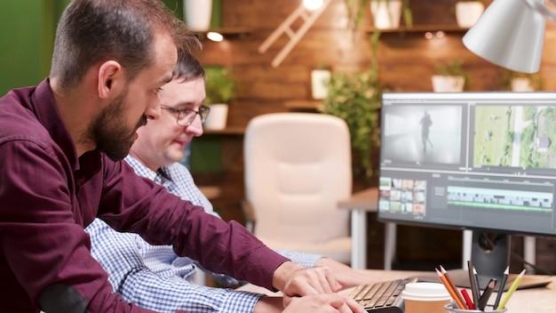 Homme producteur vidéaste éditant des séquences de film discutant des effets visuels avec le photographe