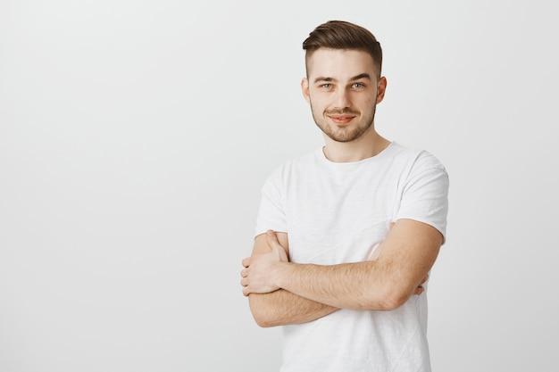 Homme professionnel confiant croise les bras et à la recherche d'un sourire déterminé