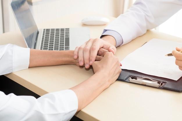 Un homme de professionnels de la santé rassurant et discutant avec une jeune femme inquiète un patient