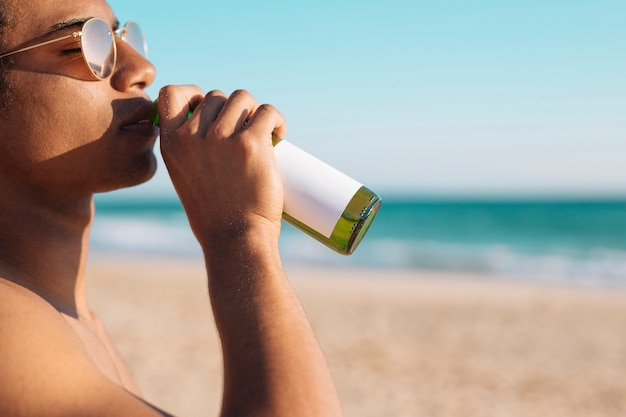 Homme profitant de la bière au bord de mer
