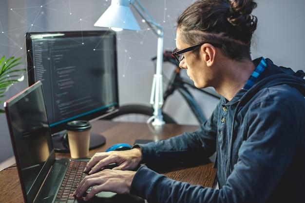 Homme programmeur écrit le code du programme sur un ordinateur portable à la maison