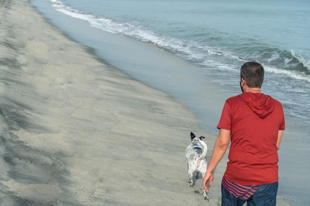 Homme promenant un chien le matin sur la plage