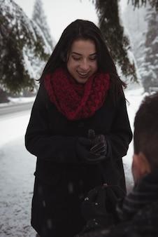Homme proposant à femme avec anneau en forêt pendant l'hiver