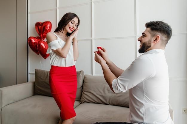 Homme proposant une fiancée avec un anneau et des ballons en forme de coeur à la maison dans l'appartement