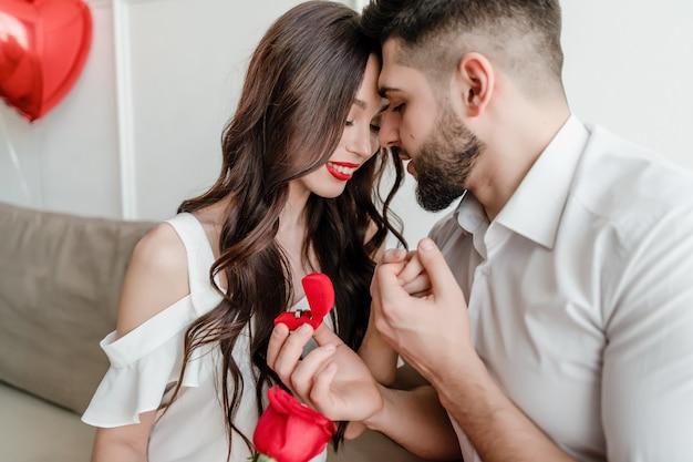 L'homme propose à la femme avec anneau et rose rouge à la maison sur un canapé avec des ballons en forme de coeur